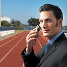 businessman on running track talking on mobile phone, portrait
