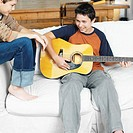 two brothers laughing and playing guitar sitting on a sofa