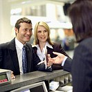 businessman and businesswoman checking in at airport and stewardess checking tickets