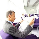 side view of businessman reading newspaper sitting in airport lounge