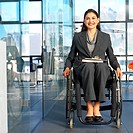 portrait of a businesswoman sitting in a wheelchair in an office