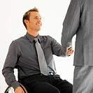 businessman sitting in a wheelchair shaking hands with a businessman standing