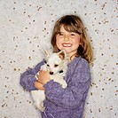 portrait of a girl (10-11) holding a puppy