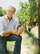 mature man holding grapes in a vineyard