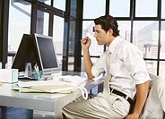 side profile of a businessman sitting in front of a computer in an office