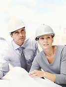 close-up of a male architect standing with a female architect holding a blueprint