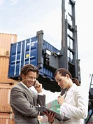 female engineer holding a clipboard and a male engineer talking on a mobile phone