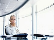 businesswoman sitting on a chair with her hand on her chin