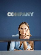 businesswoman thinking with her hand on her chin in an office