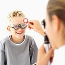 optometrist checking a boy´s (8-9) eyes