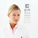 portrait of a female doctor standing with eye chart behind her
