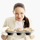 portrait of a woman holding a tray of muffins