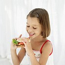 girl (6-7) holding a hamburger