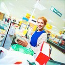 portrait of a young girl working in a supermarket at the checkout counter