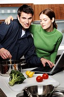 Couple using laptop while cooking in the kitchen.