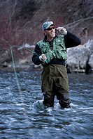 Fisherman standing in river holding rod, talking on phone