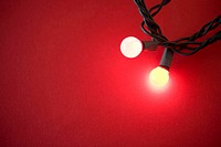 Two white fairy lights on red background, close up (soft focus)