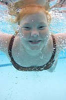 Girl (8-9), swimming underwater in pool, portrait