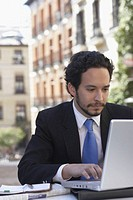 Close-up of a businessman working on a laptop outdoors