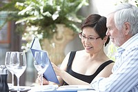 Mature man and woman looking at menu in restaurant, smiling