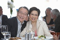 Mature man and woman dining in restaurant, smiling, portrait