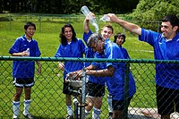 Teenage male (16-20) soccer team pouring water over teammate