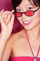 Woman adjusting sunglasses, smiling at camera