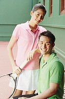 Couple in tennis outfits, looking at camera, smiling