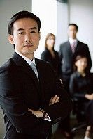 Businessman standing with arms crossed, people in the background