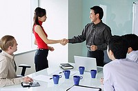 Executives exchanging shaking hands in meeting room