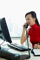 Female executive sitting at office desk, using telephone
