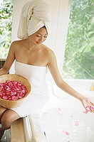 Woman in towel, sitting at edge of bath tub, throwing flower petals into water
