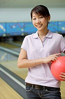 Woman at bowling alley, smiling, holding bowling ball under arm