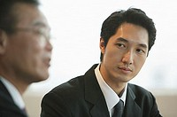 Businessman looking at person next to him