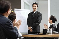 Businessman standing next to flipchart, other executives clapping