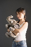 Young woman with braids hugging stuffed toy elephant