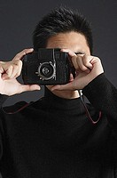 Young man dressed in black looking through camera