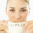 close-up of a young woman drinking a cup of cappuccino