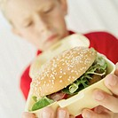 close-up of a boy holding a hamburger