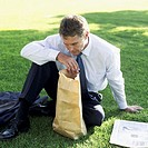 Elevated view of a businessman sitting in a lawn looking inside a brown paper bag