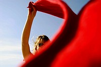 20 years old girl on beach wind blowing red towel. Kitsalano Beach. Vancouver. BC. Canada