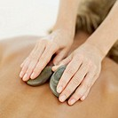 close-up of a person getting a back massage with therapeutic stones