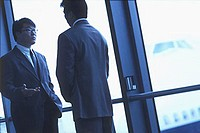 Two male executives talking in airport, silhouette