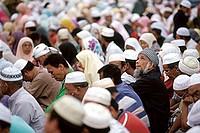 Malaysia, Kota Bahru, Muslims sit on dusty streets to listen to Pan -Malaysian Islamic Party speech.