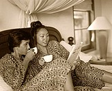 Man and woman holding cups and sharing newspaper in bed