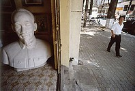 Vietnam, Ho Chi Minh City, A man walking past a large bust of Ho Chi Minh