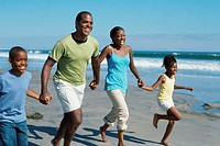 parents and their children running on the beach