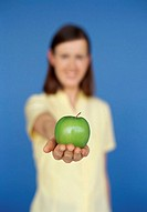 portrait of a young woman holding a green apple on her palm