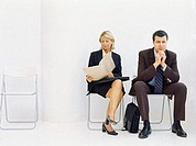 businessman and a businesswoman sitting on chairs