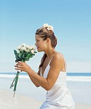 side profile of a bride holding a bouquet of flowers on the beach